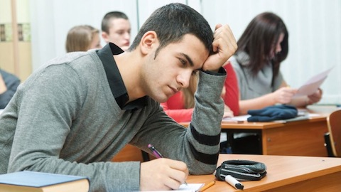 Picture of male college student taking test, looking concerned